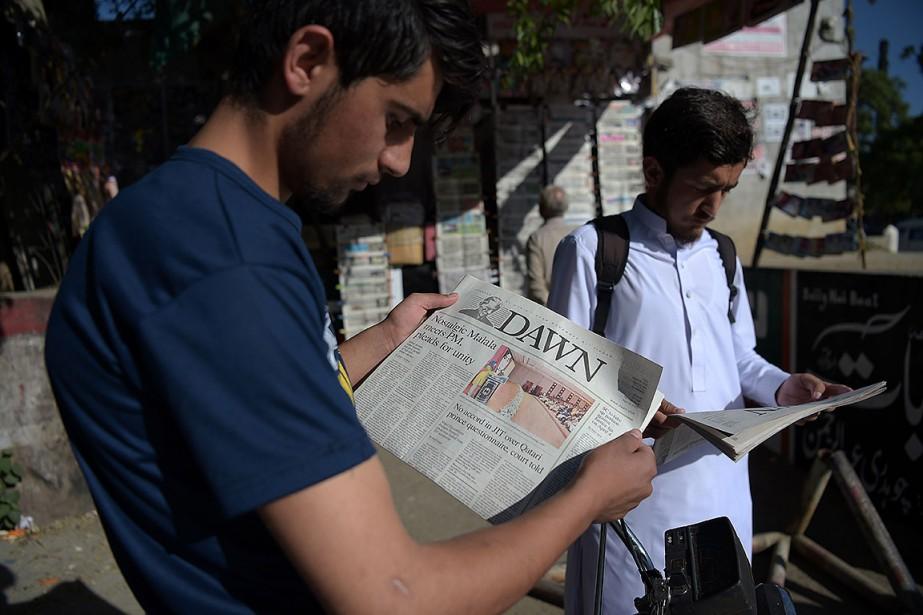 Des Pakistanais lisent des journaux qui couvrent abondamment... (AAMIR QURESHI, AFP)