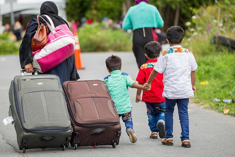 Sur cette photo, des demandeurs d'asile traversent la... (Photo Geoff Robins, archives Agence France-Presse)