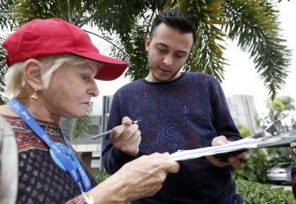 Un électeur de Miami remplit un formulaire pour...