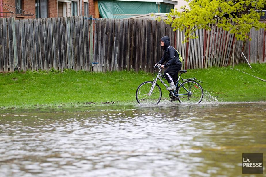 Un cycliste circule dans une rue inondée de... (PHOTO NINON PEDNAULT, ARCHIVES LA PRESSE)
