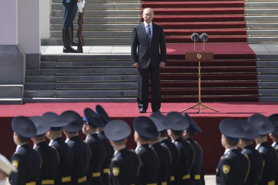 Vladimir Poutine assiste à un défilé du régiment présidentiel russe après son investiture. (Photo Agence Spoutnik, via AP)