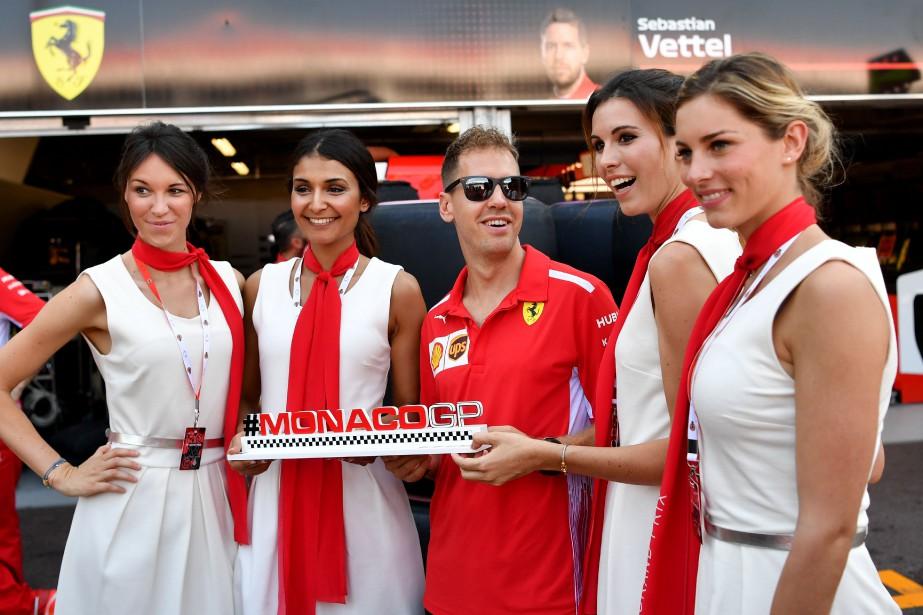Le pilote de Ferrari Sebastian Vettel pose avec des grid girls vendredi. Il a pris la défense de la tradition des grid girls, que la Formule 1 veut faire disparaître.   25 mai 2018