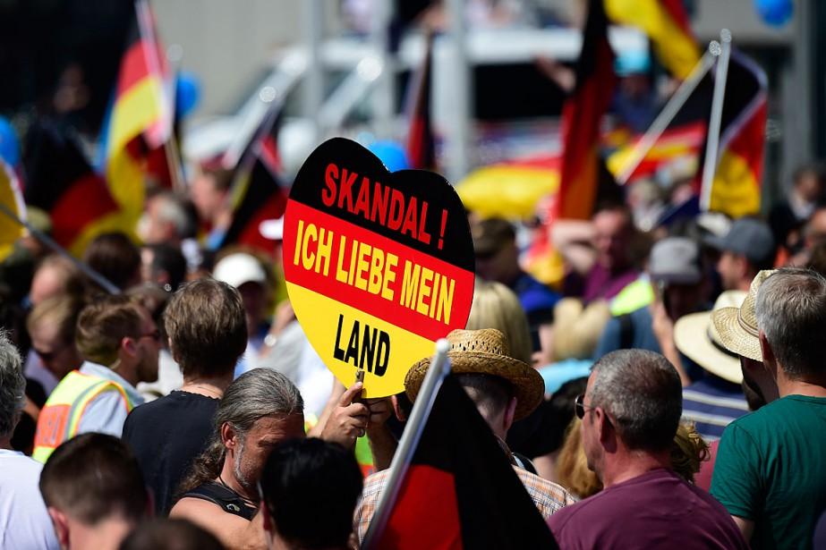 Un partisan du parti d'extrême droite AfD tient... (PHOTO TOBIAS SCHWARZ, AGENCE FRANCE-PRESSE)