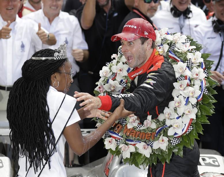 Will Power s'excuse auprès de la Reine du Festival Natalie Murdock, après l'avoir aspergée de lait en célébrant sa victoire aux 500 milles d'Indianapolis. (AP)