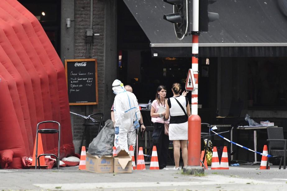 Des enquêteurs passent au peigne fin la scène... (PHOTO ERIC LALMAND, AFP)
