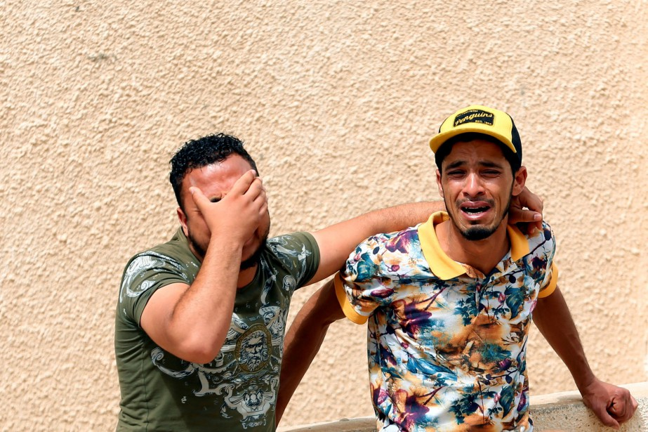 Deux hommes en pleurs quittent la morgue à... (REUTERS)