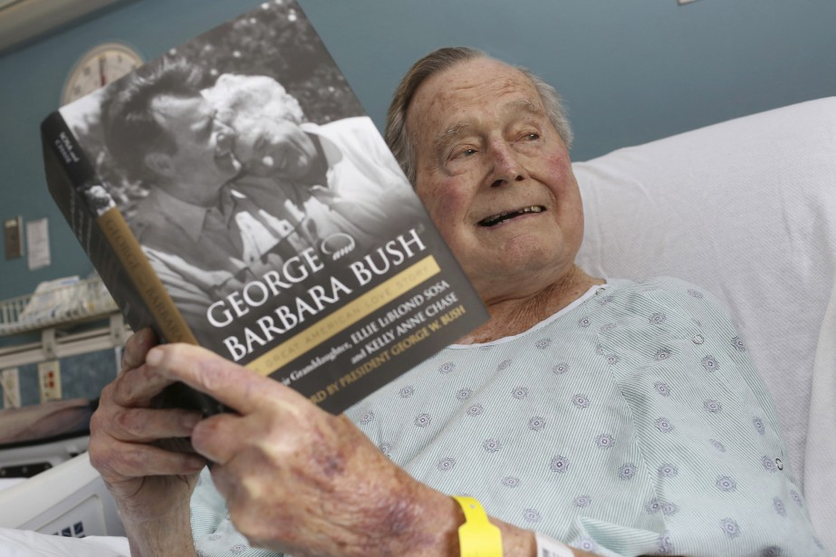 George H.W. Bush dans son lit d'hôpital lisant... (PHOTO AP)