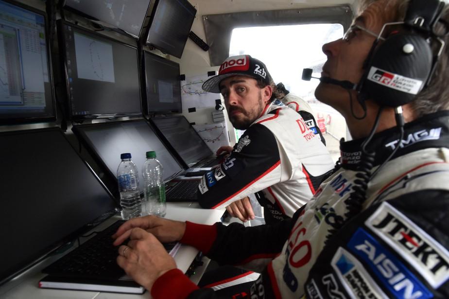 Fernando Alonso (au centre) devant les écrans vidéo acheminant les données de course des deux voitures Toyota, au poste de contrôle de l'écurie Toyota. La photo a été prise pendant un relais fait par un des autres pilotes. (AFP)