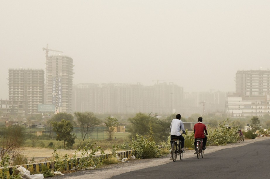 Cyclists pedal on a road enveloped by a... (Photo R. S. Iyer, Associated Press)