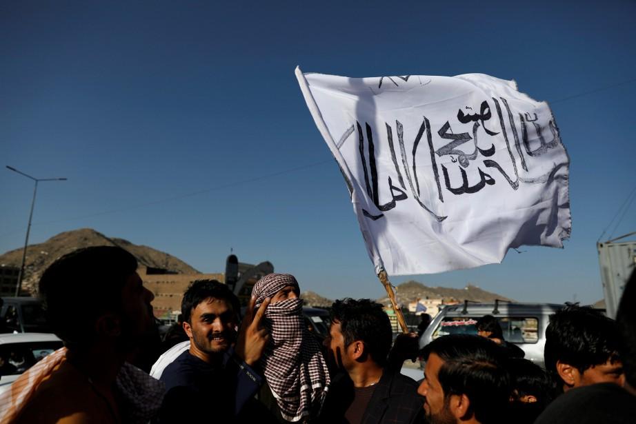 Un membre des talibans parade à Kaboul dimanche... (PHOTO REUTERS)