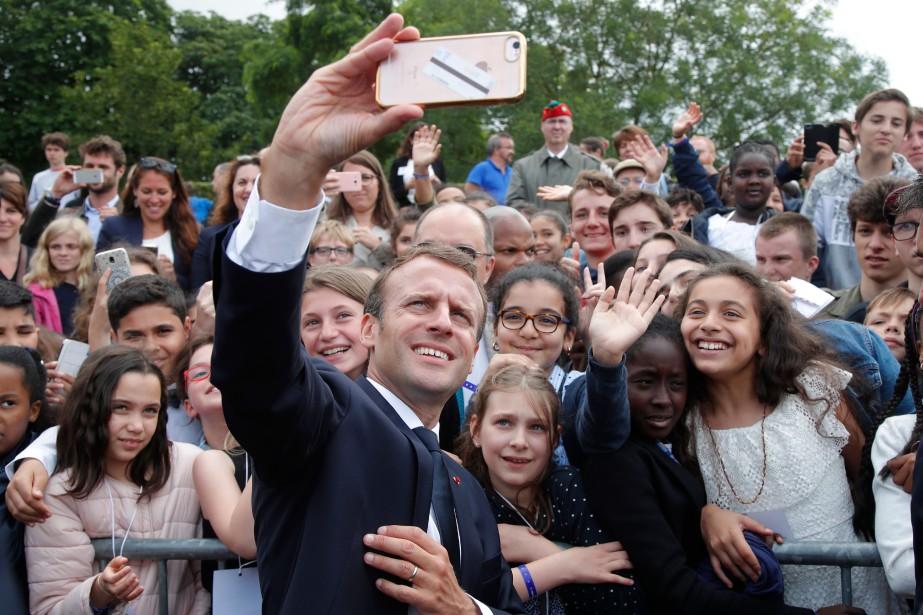 Emmanuel Macron prend un selfie avec des jeunes... (PHOTO AFP)