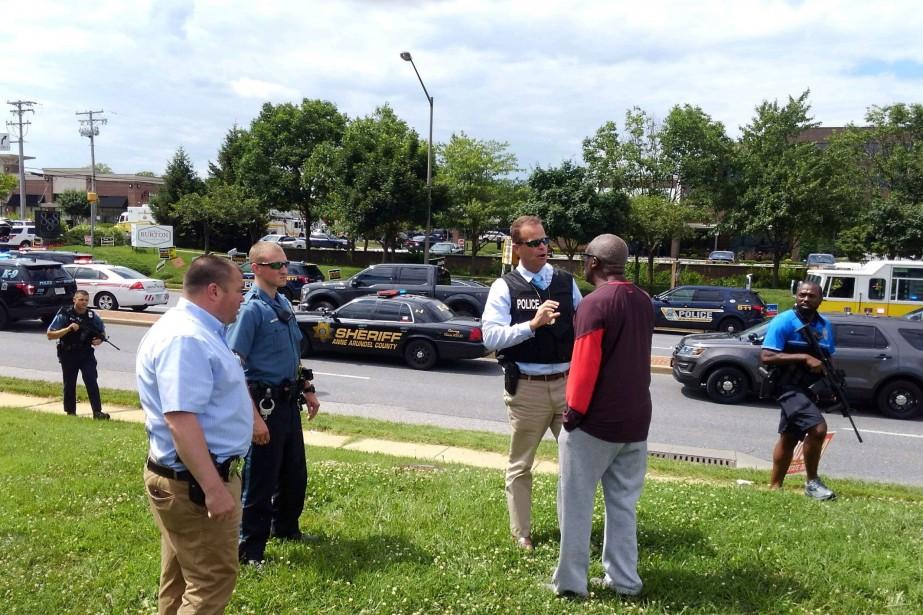 Des policiers discutent avec un témoin sur la... (PHOTO REUTERS)