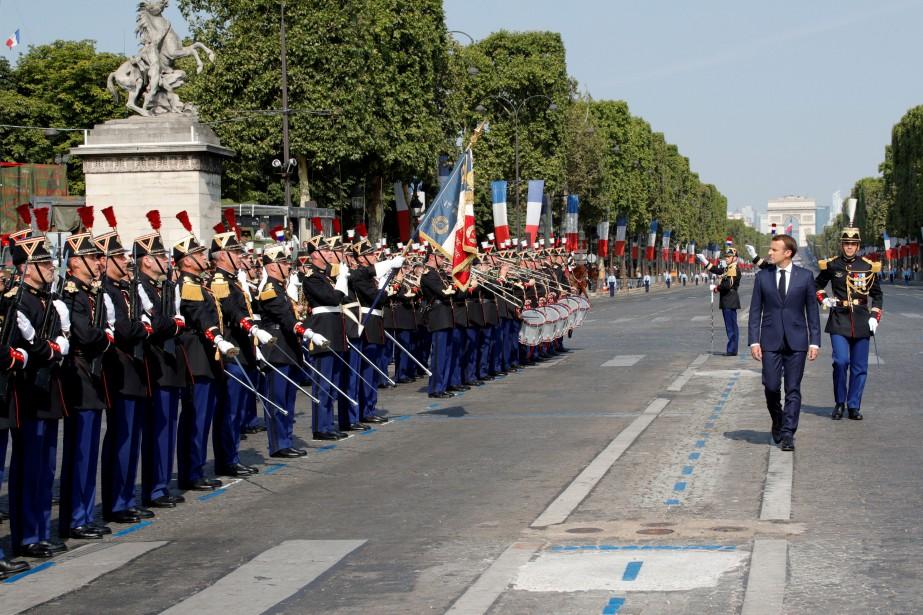 Le président Emmanuel Macron passe en revue les... (PHOTO Philippe Wojazer, REUTERS)