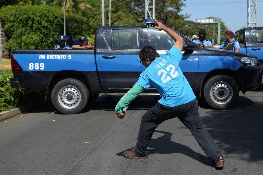 Un pasteur chrétien manifeste devant les policiers.... (PHOTO MARVIN RECINOS, AGENCE FRANCE-PRESSE)