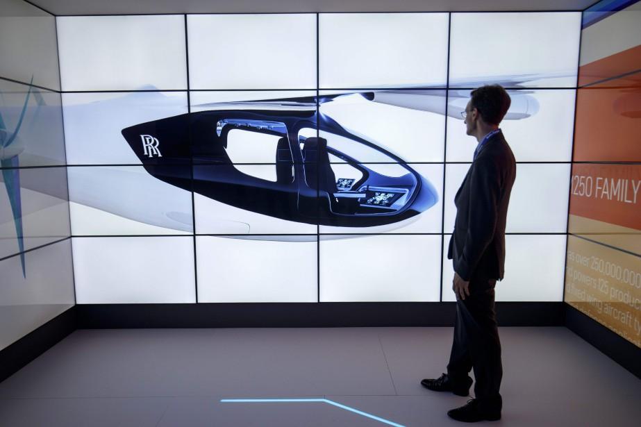 Un visiteur regarde les écrans présentant le taxi volant EVTOL de Rolls-Royce à Farnborough. (photo AFP)