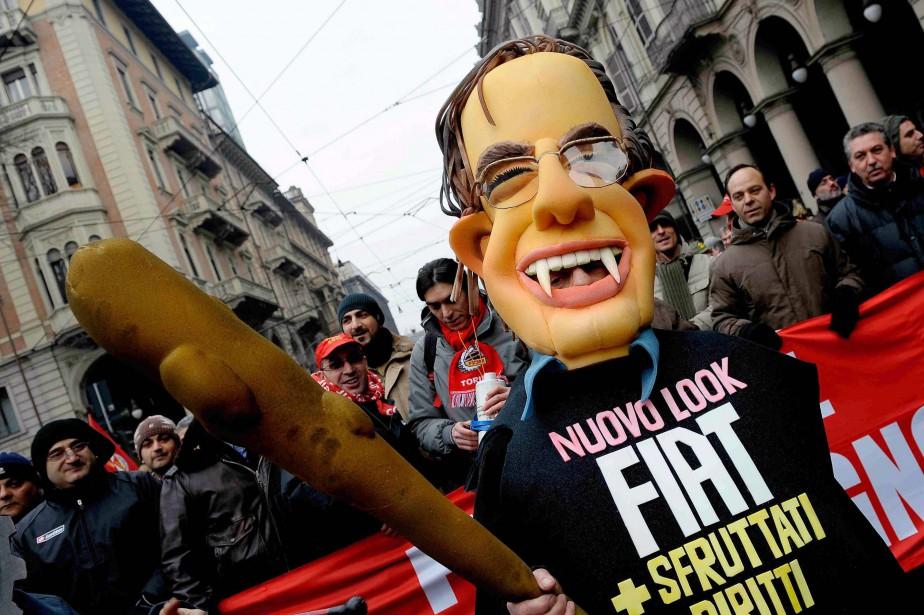 Un manifestant déguisé en Sergio Marchionne vampire porte un gourdin et un t-shirt dont le message est : «Le Fiat nouveau : moins de droits, plus d'exploitation», après que la compagnie ait adopté de nouvelles règles dans deux usines italiennes. La photo a été prise le 28 janvier 2011 à Turin. (AP)