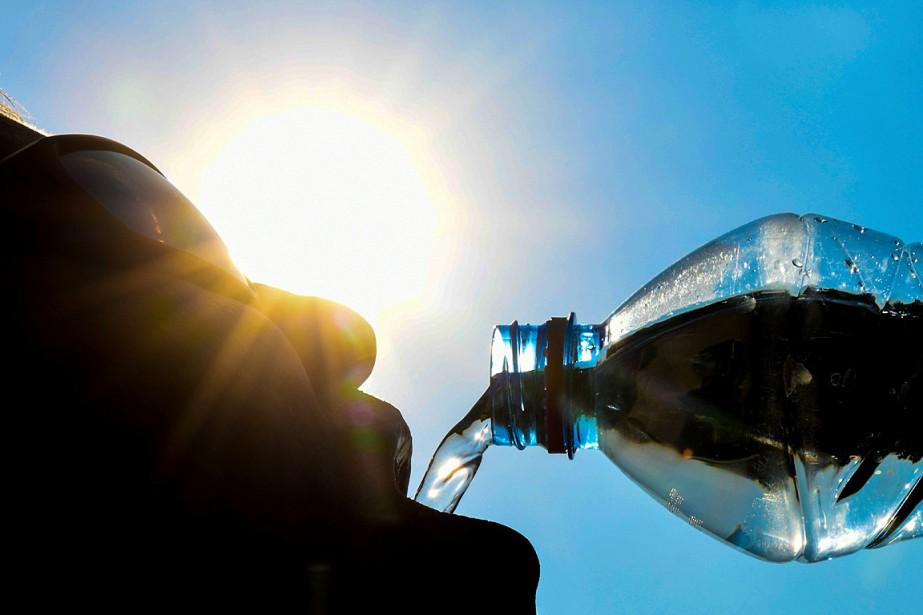 Un homme prend une gorgée d'eau sous le... (PHOTO DENIS CHARLET, AGENCE FRANCE-PRESSE)