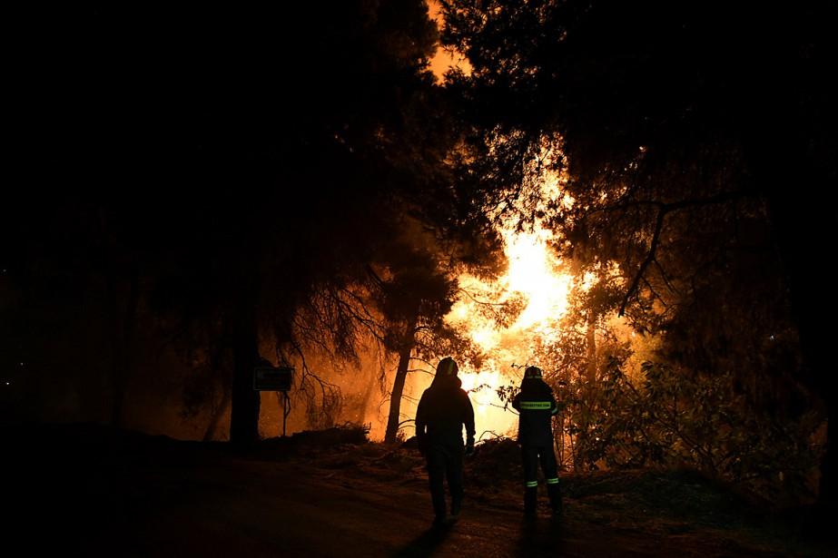 Des pompiers observent l'évolution de l'incendie qui brûle... (PHOTO MICHALIS KARAGIANNIS, REUTERS)