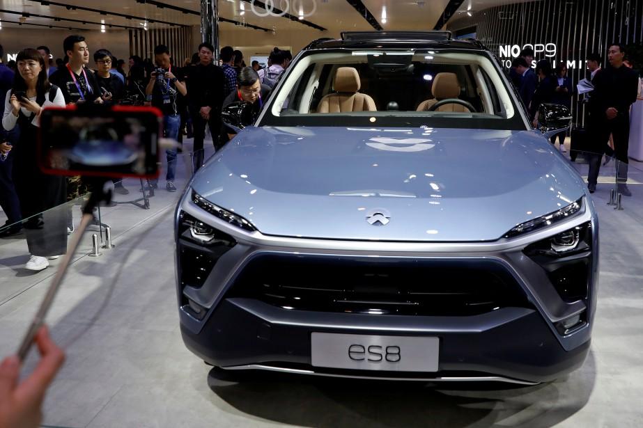 Des visiteurs au Salon de l'auto de Pékin 2018 examinent le VUS électrique NIO ES8. (photo REUTERS)