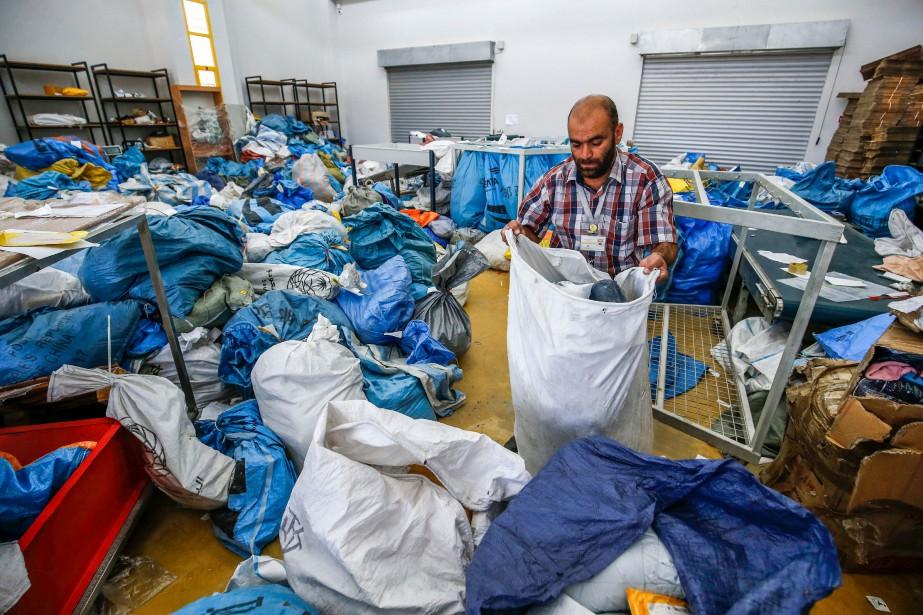 Les gros sacs colorés contenant enveloppes noircies et... (PHOTO ABBAS MOMANI, AFP)