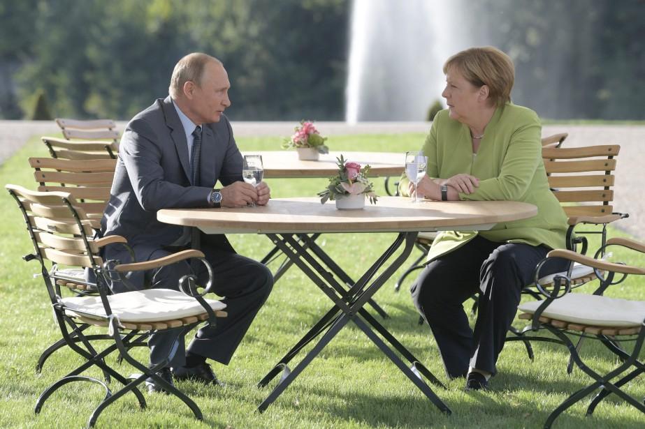 Vladimir Poutine en compagnie de la chancelière allemande,... (PHOTO Alexei Druzhinin, SPUTNIK/AP)