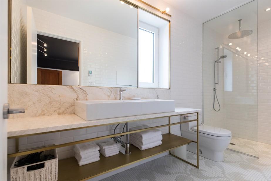 Le choix de matériaux nobles est légion dans toute la maison, y compris dans la salle de bains attenante à la chambre principale. Le sol y est revêtu d'une mosaïque de pâte de verre, le comptoir et le dosseret, de marbre, et la structure du meuble-lavabo réalisée par les artisans de l'Atelier Gris est en laiton. «La fenêtre est intégrée au miroir. Ce sont ces petits détails qui font toute une différence», souligne Renée d'Amours. (Photo Hugo-Sébastien Aubert, La Presse)