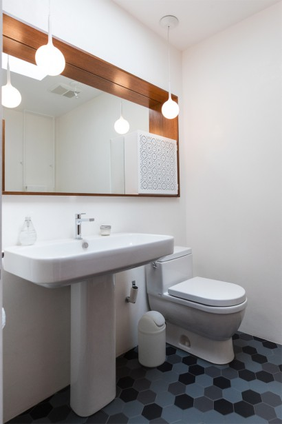 Cette deuxième salle de bains réservée aux invités arbore un plancher de céramique hexagonale remarquable par l'union originale de ses couleurs. On retrouve ici l'idée de grand miroir où se niche un autre élément. En effet, l'architecte a préféré inclure un rangement artisanal en métal peint (L'Atelier Gris) orné d'une façade ajourée plutôt qu'une pharmacie classique directement intégrée au miroir. (Photo Hugo-Sébastien Aubert, La Presse)