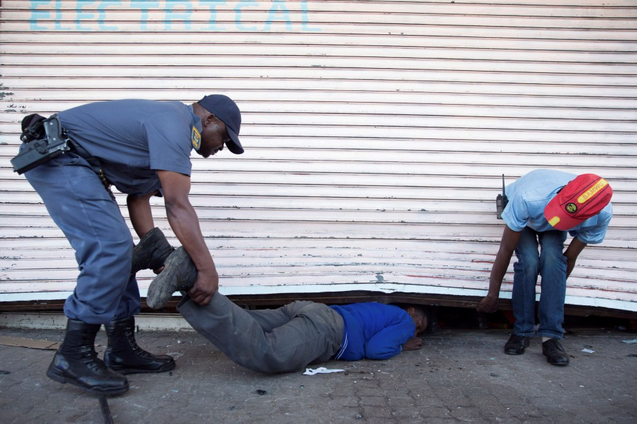 Un policier sud-africain intercepte un jeune qui tente... (Photo JAMES OATWAY, REUTERS)