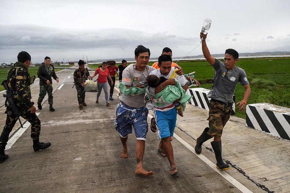 Des soldats philippins aident une famille à évacuer... (PHOTO TED ALJIBE, AGENCE FRANCE-PRESSE)