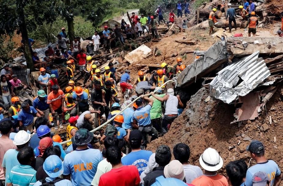Des recherches sont effectuées après qu'une colline se... (PHOTO ERIK DE CASTRO, REUTERS)