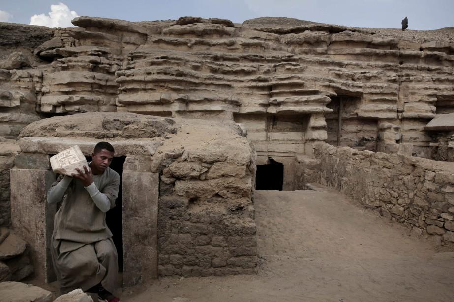 Un homme transporte un artéfact retrouvé dans une... (Photo Nariman El-Mofty, Associated Press)