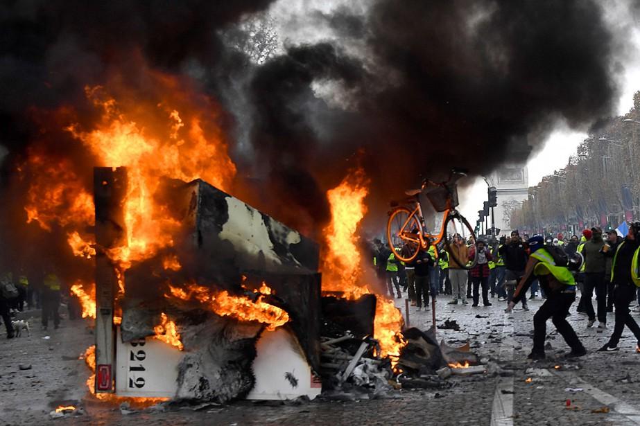 Un homme lance un vélo sur un camion... (Photo BERTRANDGUAY, Agence France-Presse)