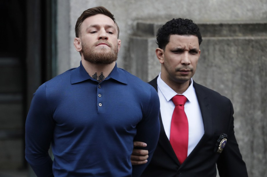 Conor McGregor se fait escorter après son arrestation... (Photo Julio Cortez, AP)