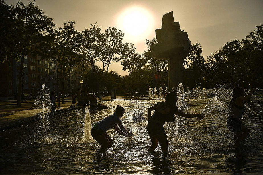 Des gens se rafraîchissent dans une fontaine de... (Photo Alvaro Barrientos, archives Associated Press)