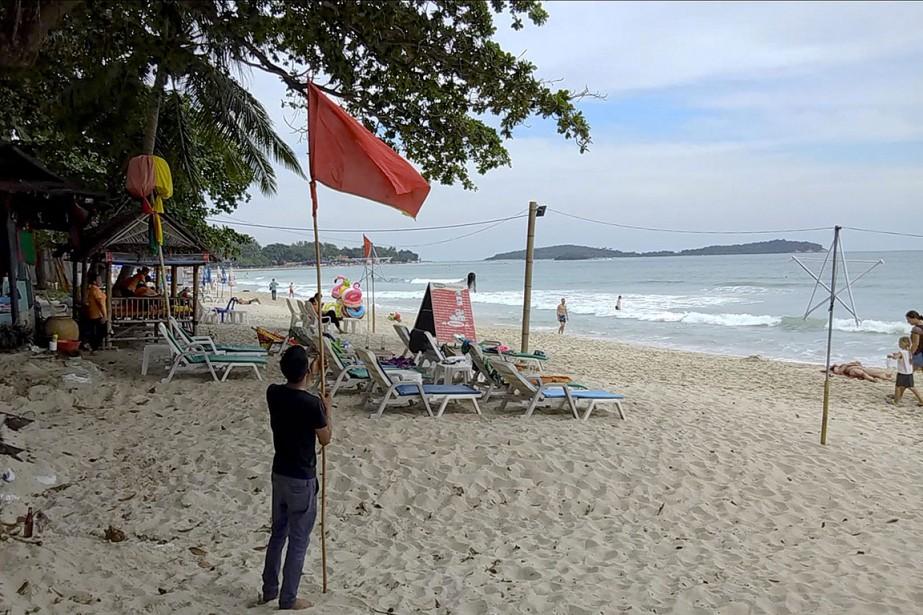 Un homme installe un drapeau rouge sur la... (Photo Sithipong Charoenjai, AP)