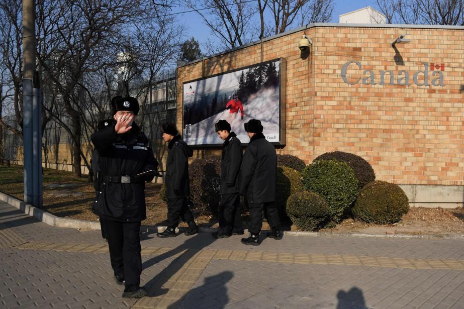Des officiers chinois tentent de disperser les caméras... (PHOTO AFP)