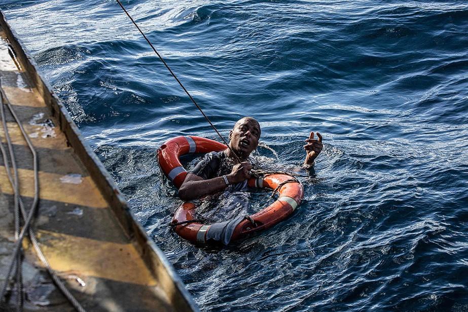 Un migrant est secouru après avoir plongé dans... (Photo FEDERICO SCOPPA, Agence France-Presse)