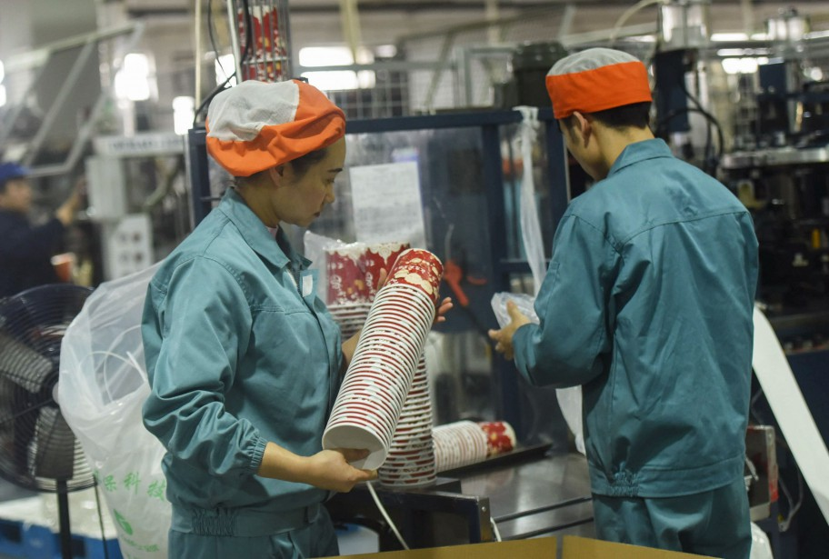 Employees check paper bowls at a factory in... (Photo STR, AFP)