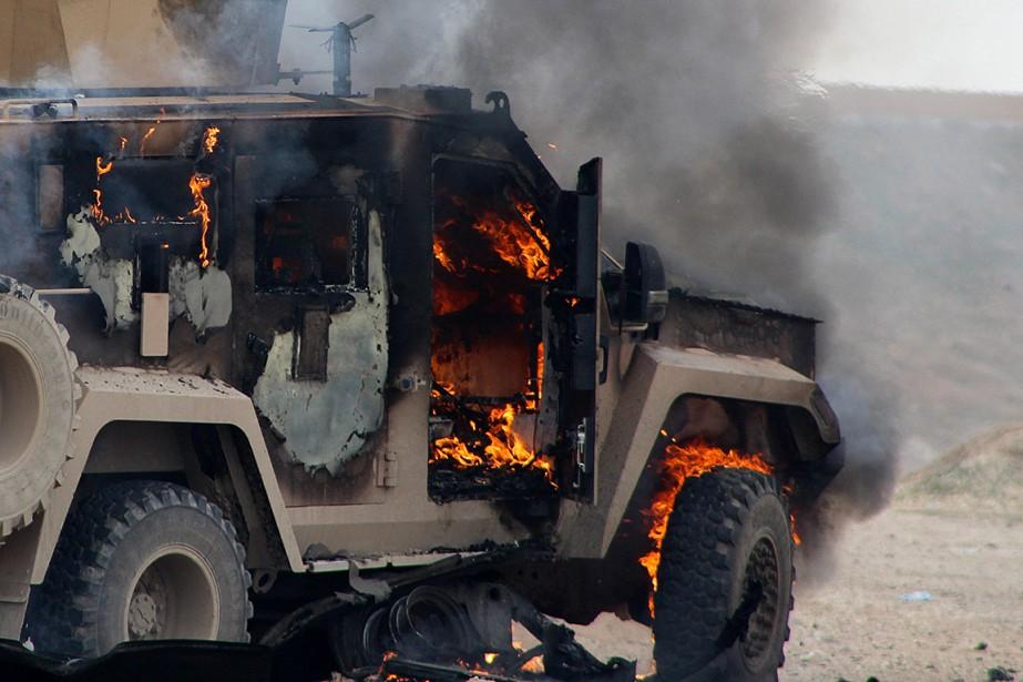 Un véhicule militaire en flammes sur le site... (Photo agence Archives France-Presse)