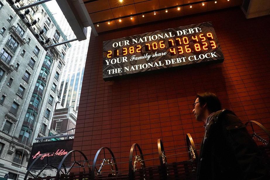 Un homme passe devant une horloge indiquant le... (Photo TIMOTHY A. CLARY, Agence France-Presse)