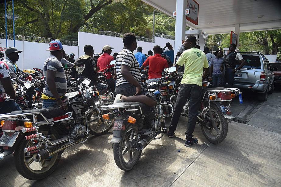 Des clients patientent pour obtenir de l'essence dans... (Photo HECTORRETAMAL, Agence France-Press)