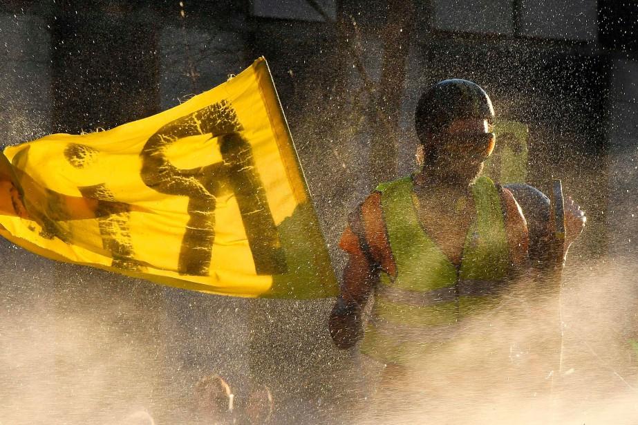 Un protestataire est aspergé par un canon à... (PHOTO GEORGES GOBET, ARCHIVES AFP)