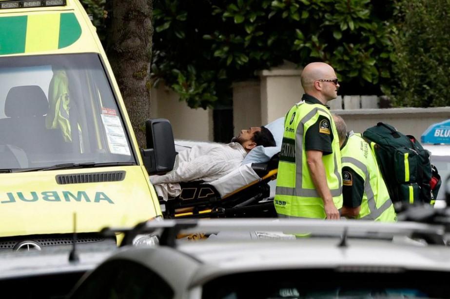 Des ambulanciers portent secours à un homme blessé... (PHOTOMARKBAKER, ASSOCIATED PRESS)