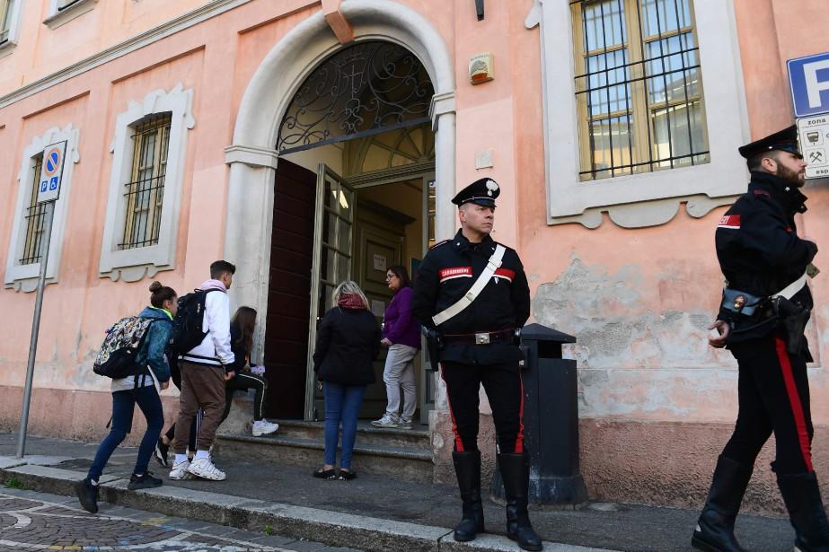 Des carabiniers surveillent l'entrée de l'école Giovanni Vailati,... (PHOTO AFP)
