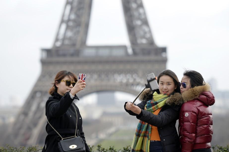 Des touristes chinoises se photographient devant la Tour... (PHOTO MIGUEL MEDINA, ARCHIVES AFP)